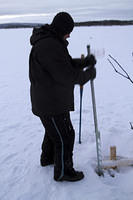 Sawing a hole in the ice to retrieve the net